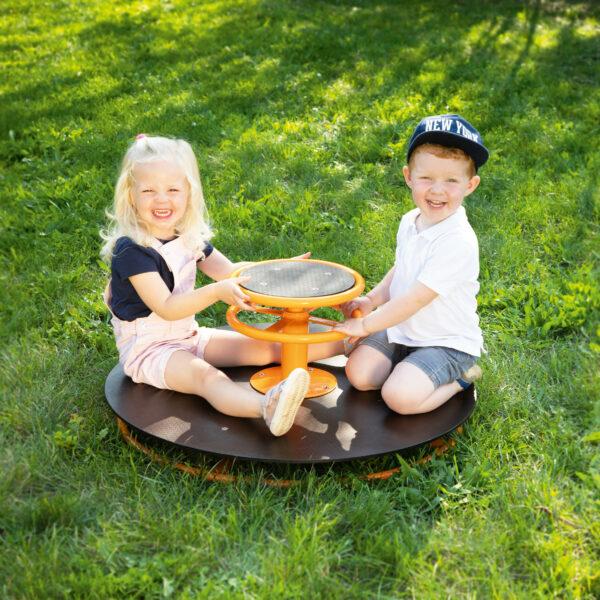 Kinder sitzen auf Toptrike Karussell
