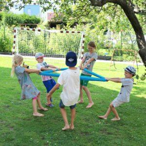 Kinder spielen mit Erlebnistuch im Garten