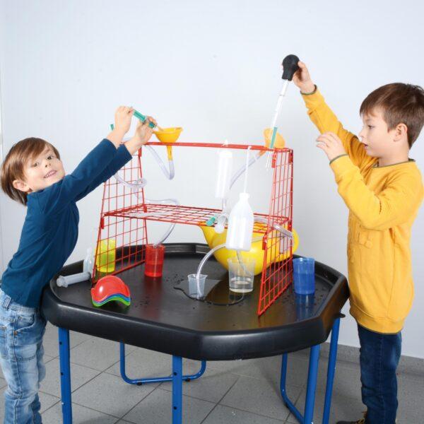 Kinder experimentieren am Wasserspielständer