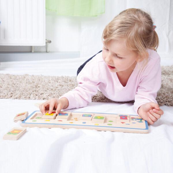 Kind spielt mit Legepuzzle Formenzug