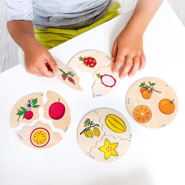 Kind spielt mit Lernpuzzle Früchte