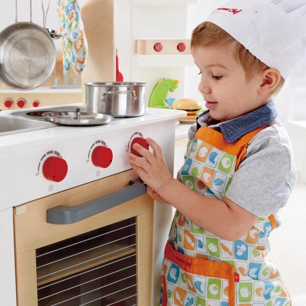 Kind spielt mit Kinderküche ausziehbar