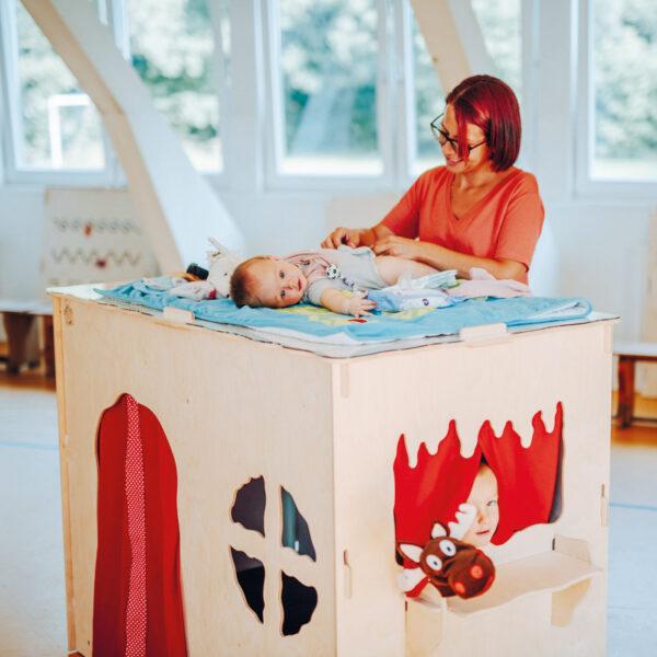 Kind wird auf dem KuWiH Spielhaus gewickelt