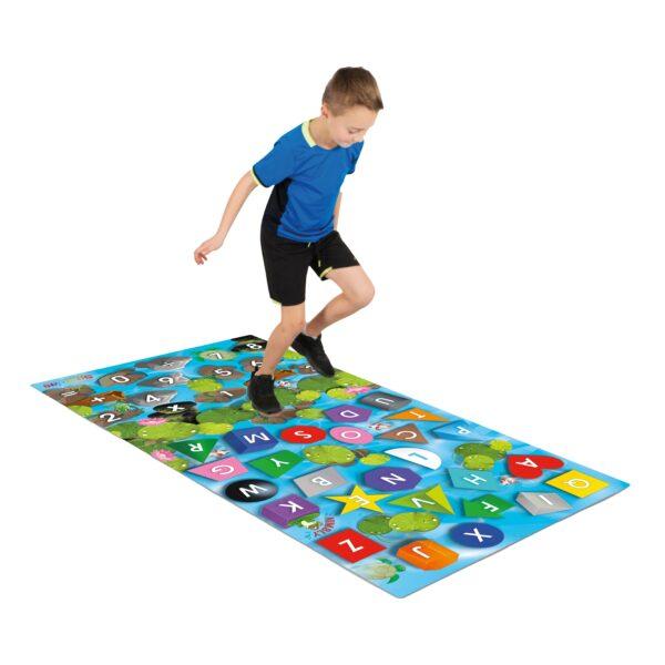 Kind hüpft auf Spiel- und Lernteppich