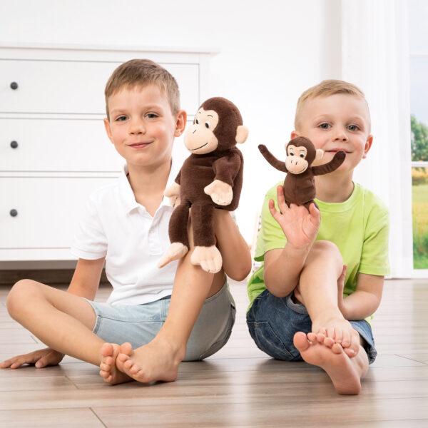 Kind spielt mit Mutter Kind Handpuppe Affe