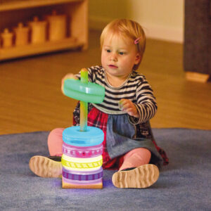 Kind spielt mit Sensorik Stapelspiel